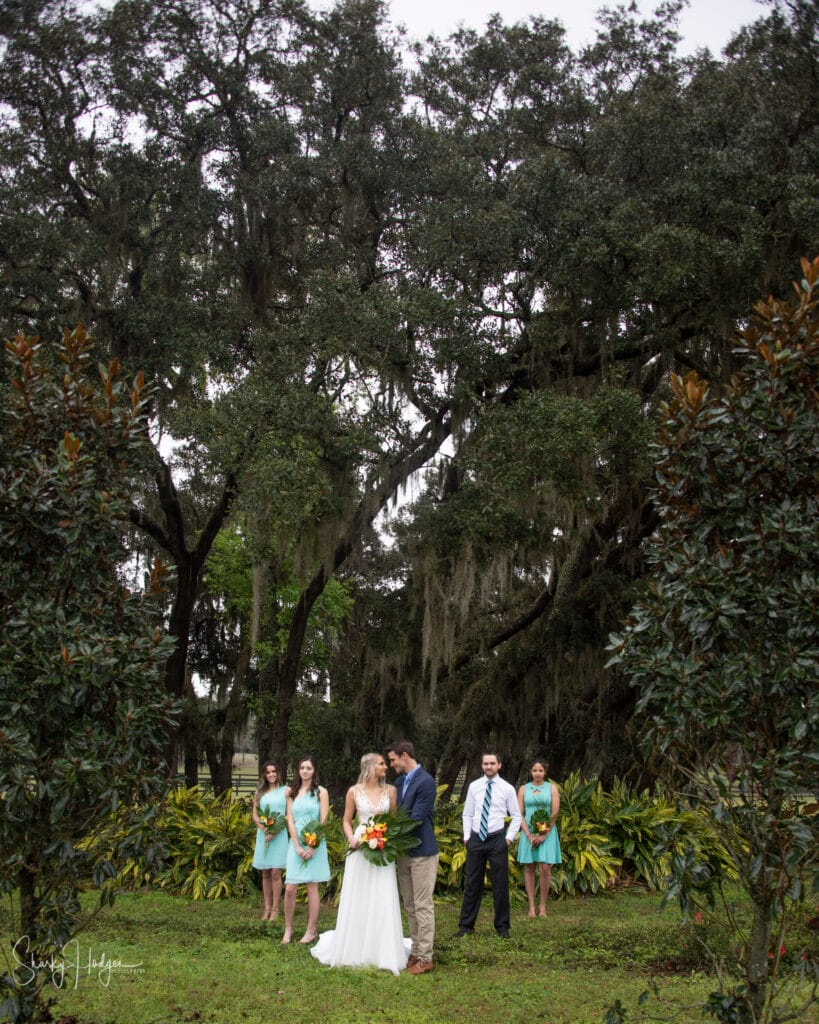 bride and groom with bright flowers standing in front of large oak trees