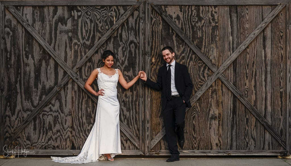 bride and groom holding hands in front of large rustic wood doors