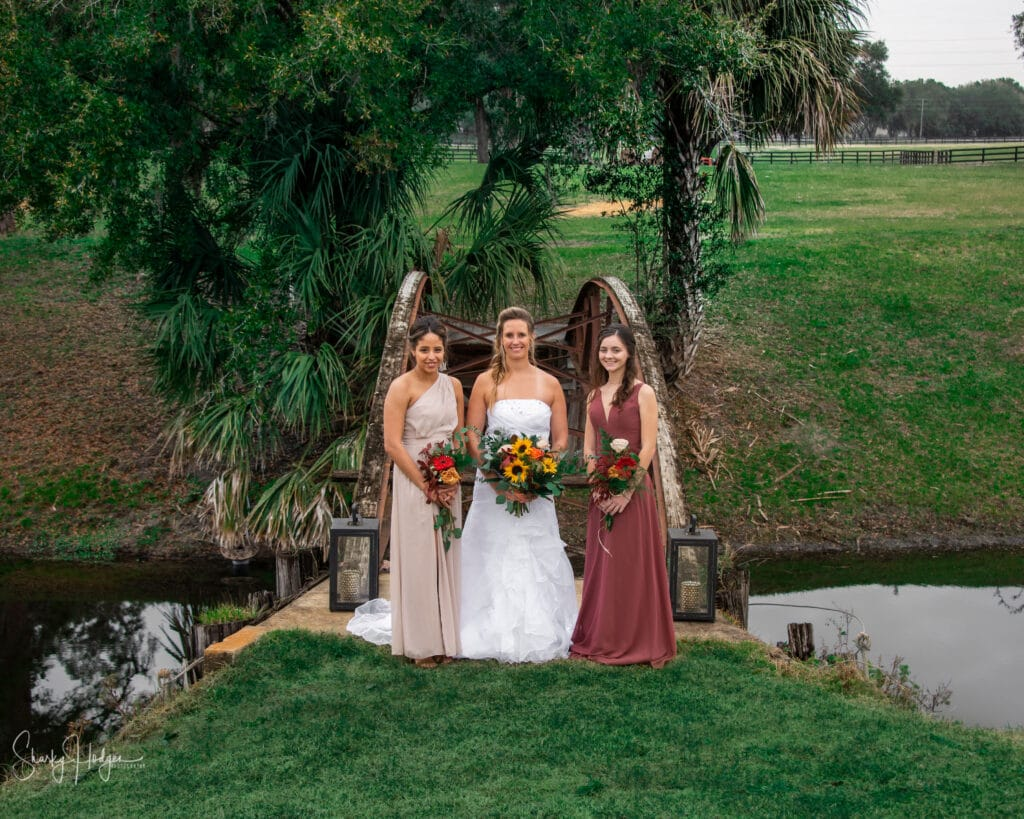 bride and two bridesmaids in front of small bridge