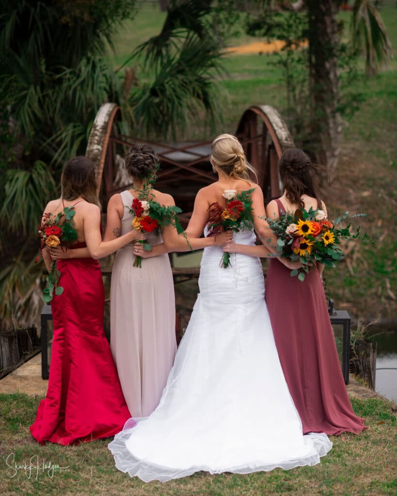 bride and bridesmaids with different red dresses on holding fall flowers