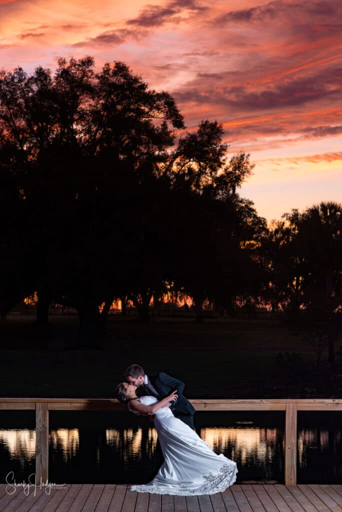 bride and groom kissing on dock at sunset