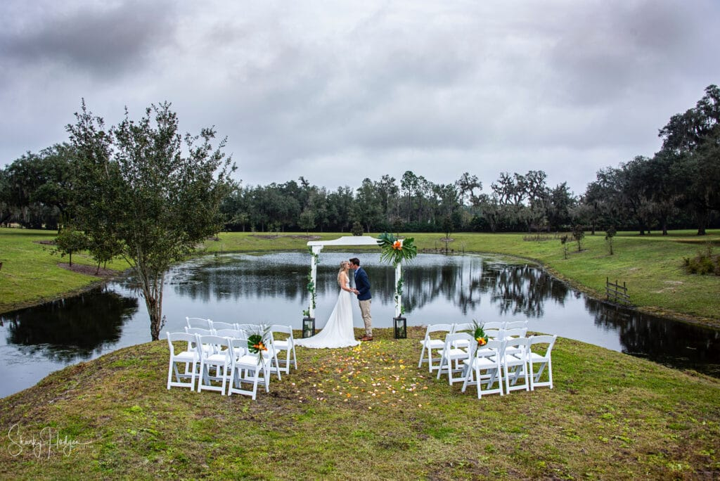 outdoor wedding with white chairs and arch in front of lake
