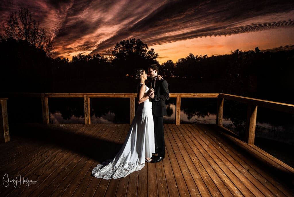 bride and groom dancing on dock at sunset