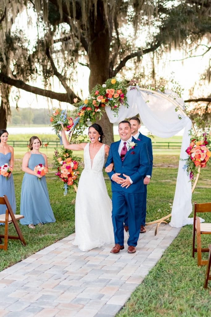 Jill-Heaton-Event-Decor-Bride and Groom walking down aisle away from floral arch