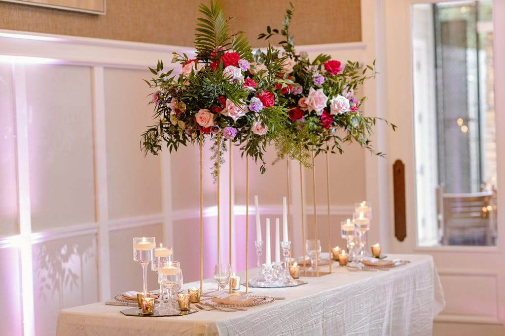 pink floral arrangements with lots of greenery in tall glass vases on table for wedding reception