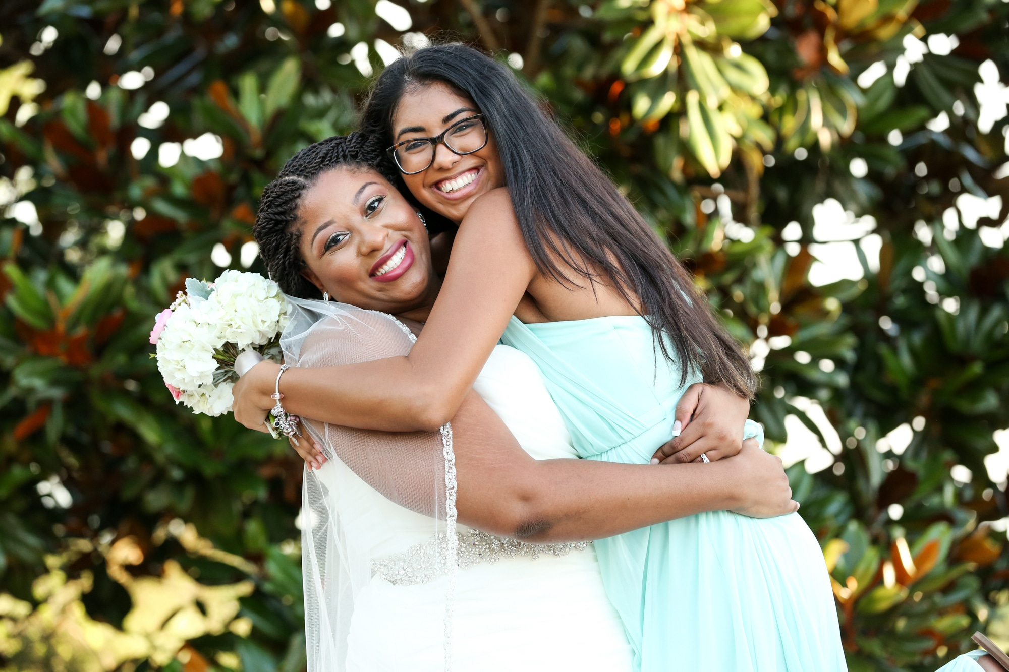 bride and bridesmaid in mint green bridesmaid dress with huge smiles hugging