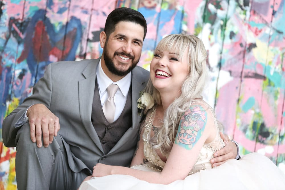bride with tattoos and groom smiling portrait in front of graffiti wall