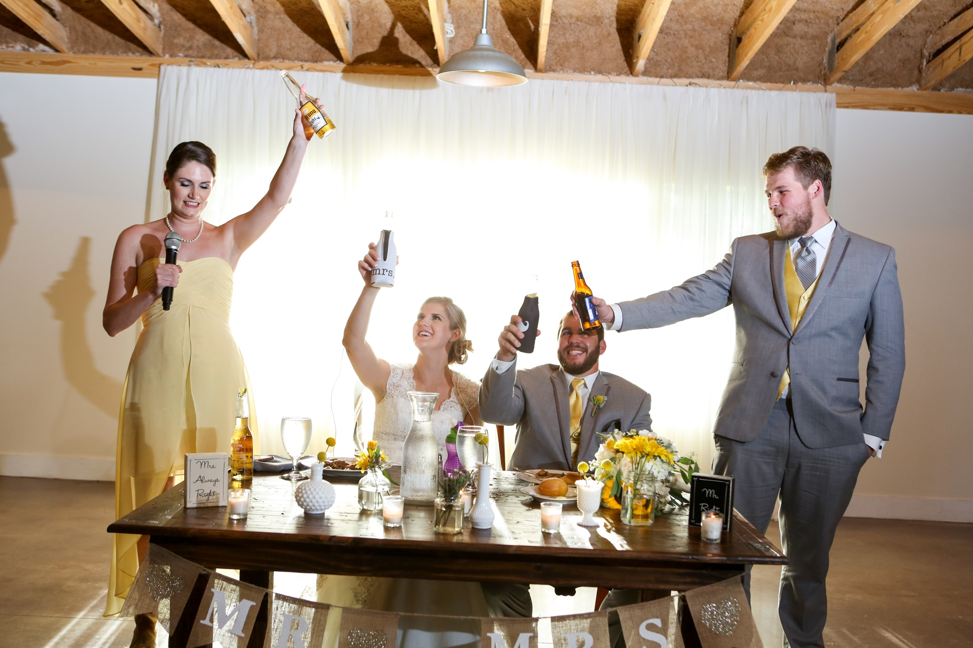 bride and groom at sweetheart table during wedding toasts with best man and maid of honor