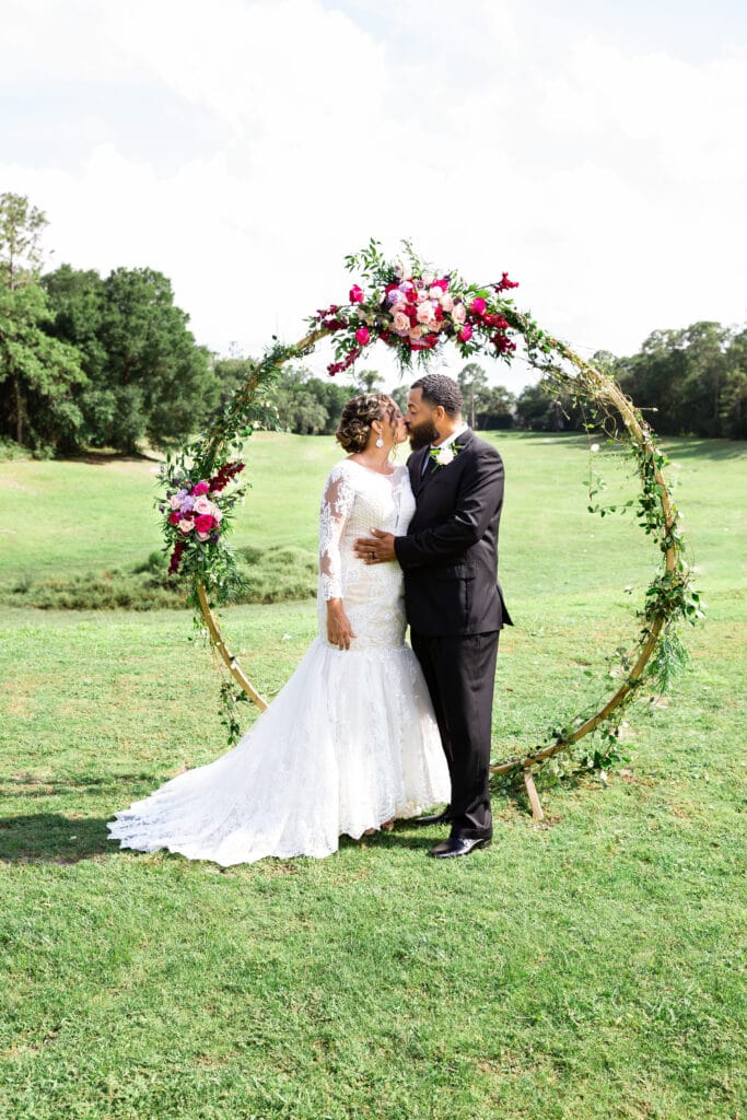 bride and groom kissing in front of wedding arch covered in greenery and pink florals