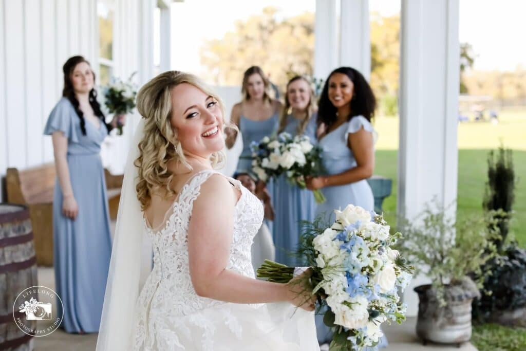 bride looking over her shoulder and smiling at camera with bridesmaids in blue dresses in the background