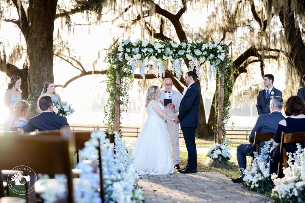 bride and groom getting married in outdoor ceremony with white floral arch and large oak trees