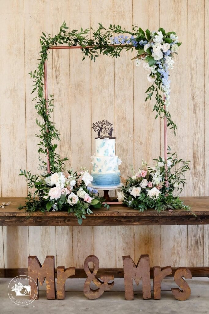 blue and white wedding cake surrounded in floral bouquets and garland