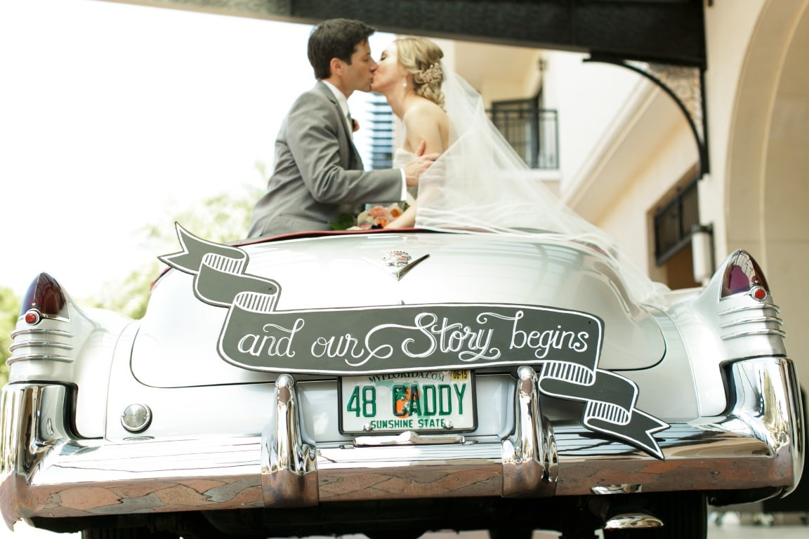 couple kissing in a vintage car with sign on the back