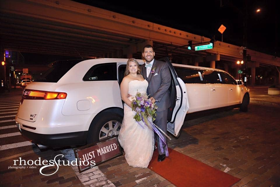 couple standing next to a white stretch limousine