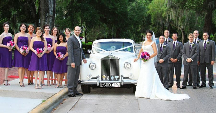 bride & groom with bridal party standing next to vintage car