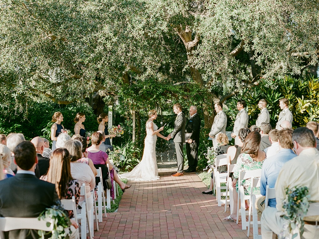 outdoor wedding ceremony with white chairs, brick pathway, and large trees