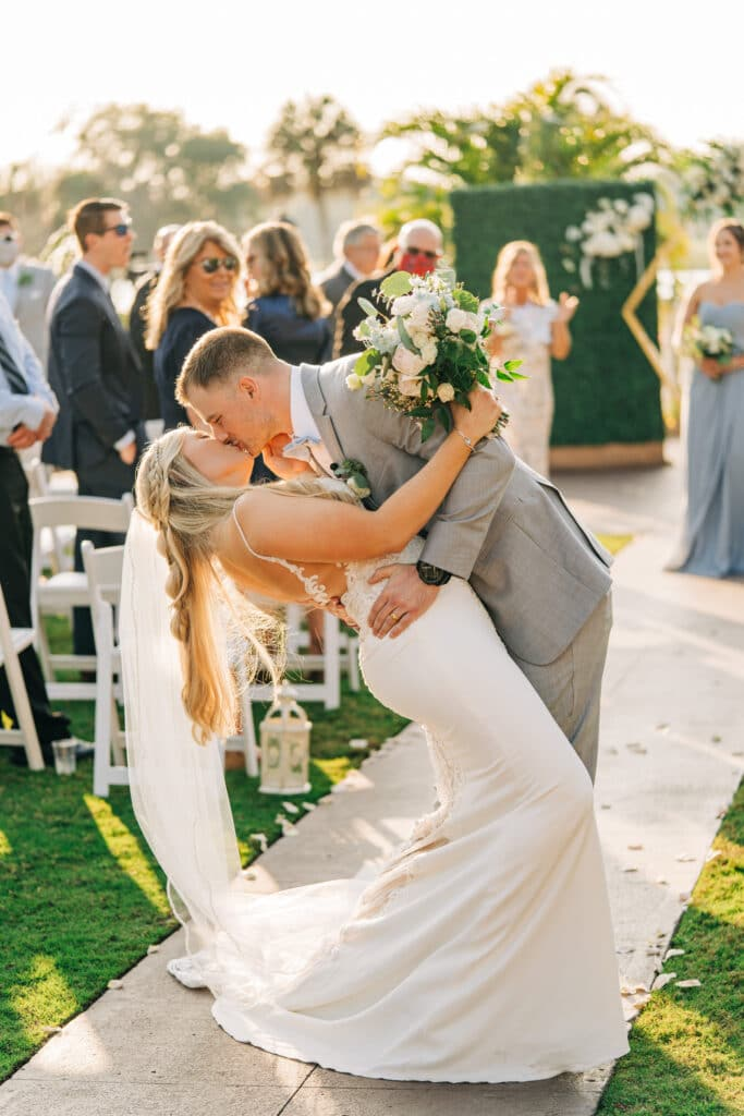 groom in gray tux kissing bride just after getting married with guests clapping in the background