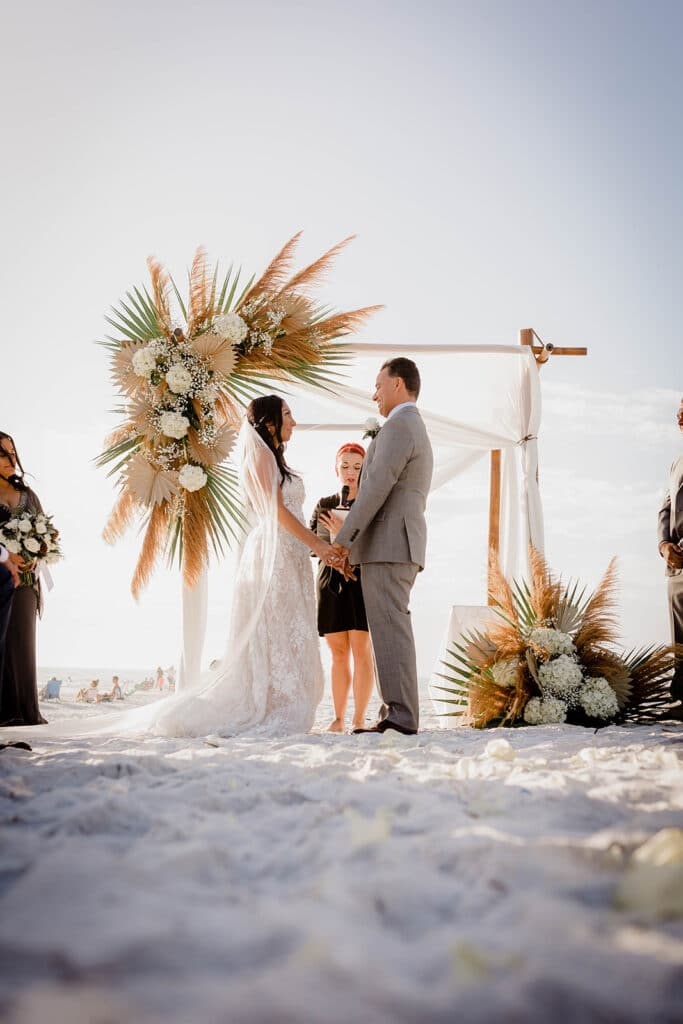 bride and groom getting married on beach under wooden arch with large floral arrangement on it