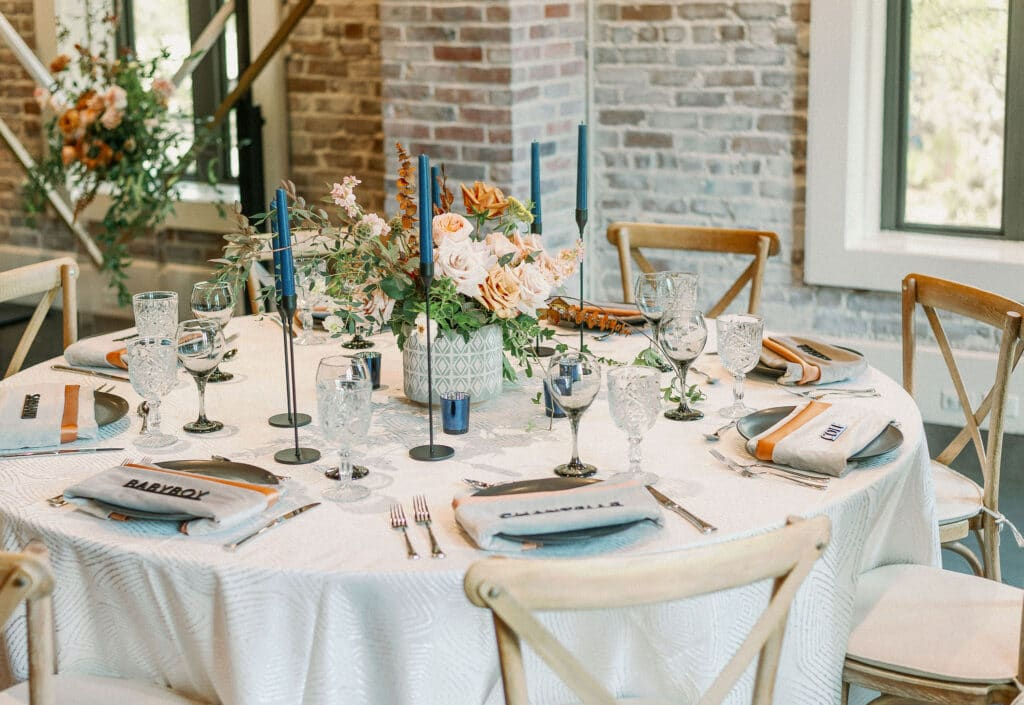 wedding reception table with blue candlesticks in front of whitewashed brick wall