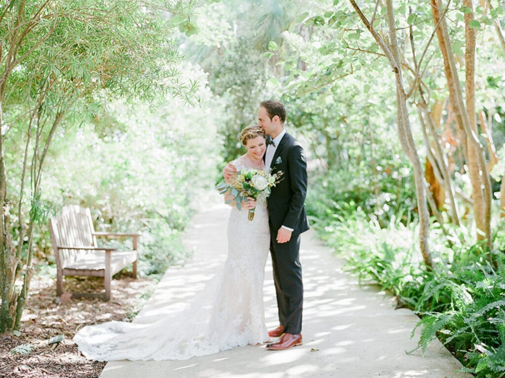 bride and groom standing under trees on pathway