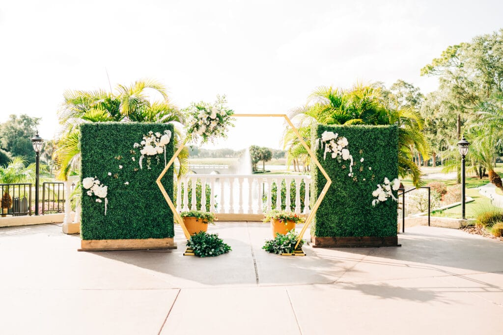 outdoor wedding ceremony set up with gold hexagon arch and green flower walls