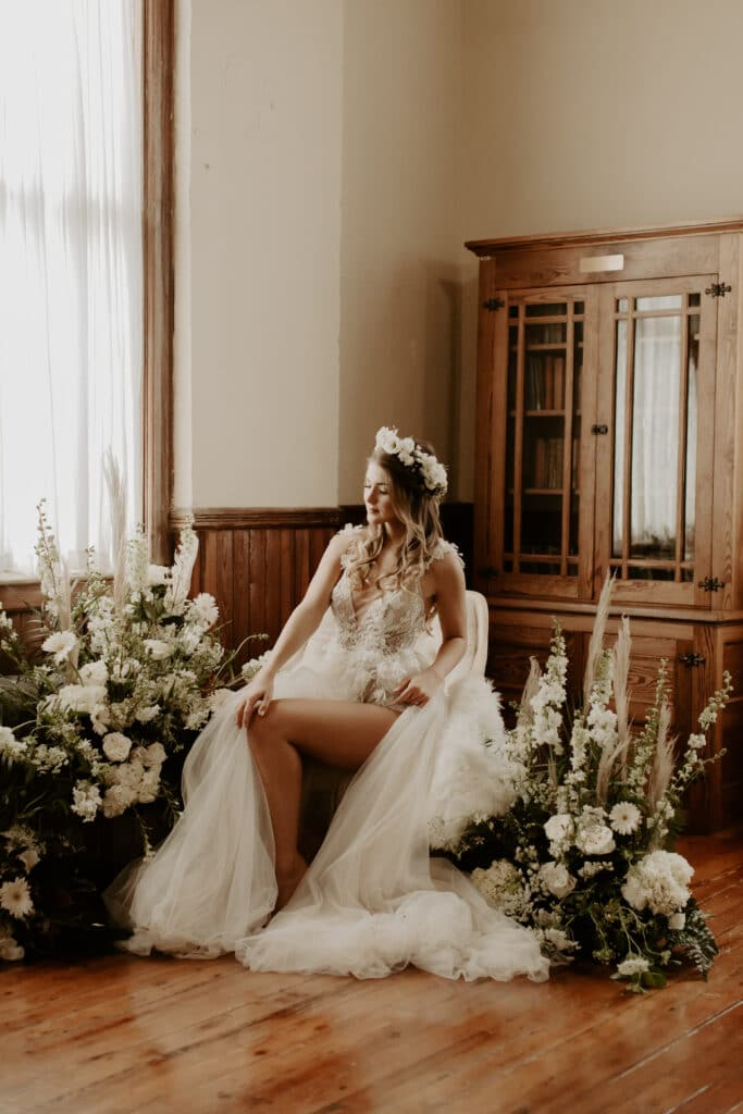 bride sitting in chair with legs showing through slit in dress surrounded by large floral arrangements
