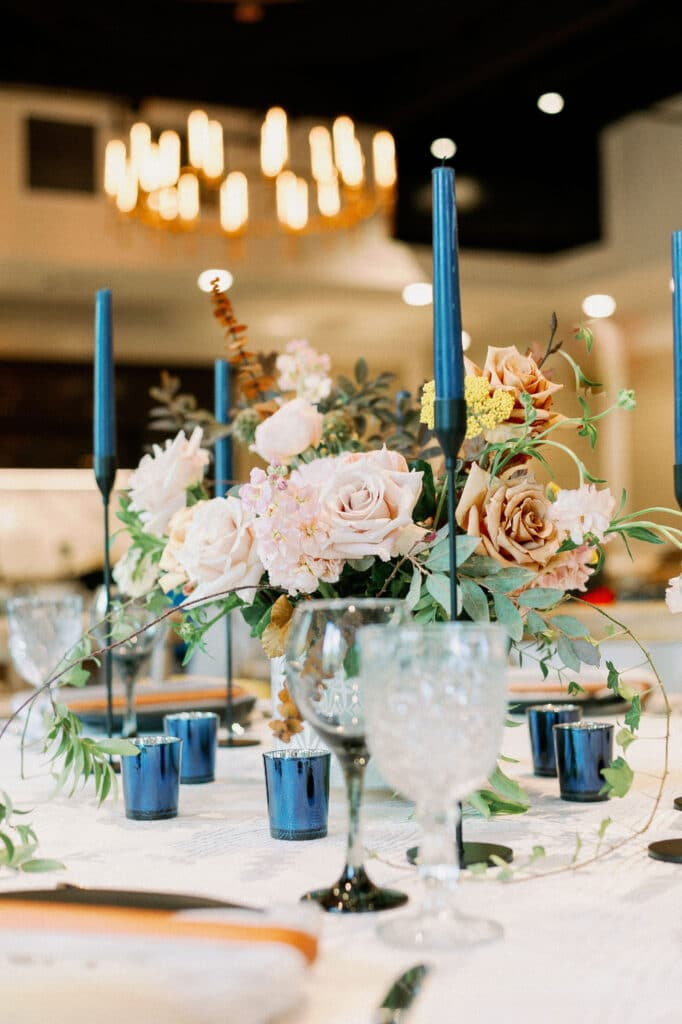 wedding table decor with blue candles, light pink flowers, and chandelier hanging in background