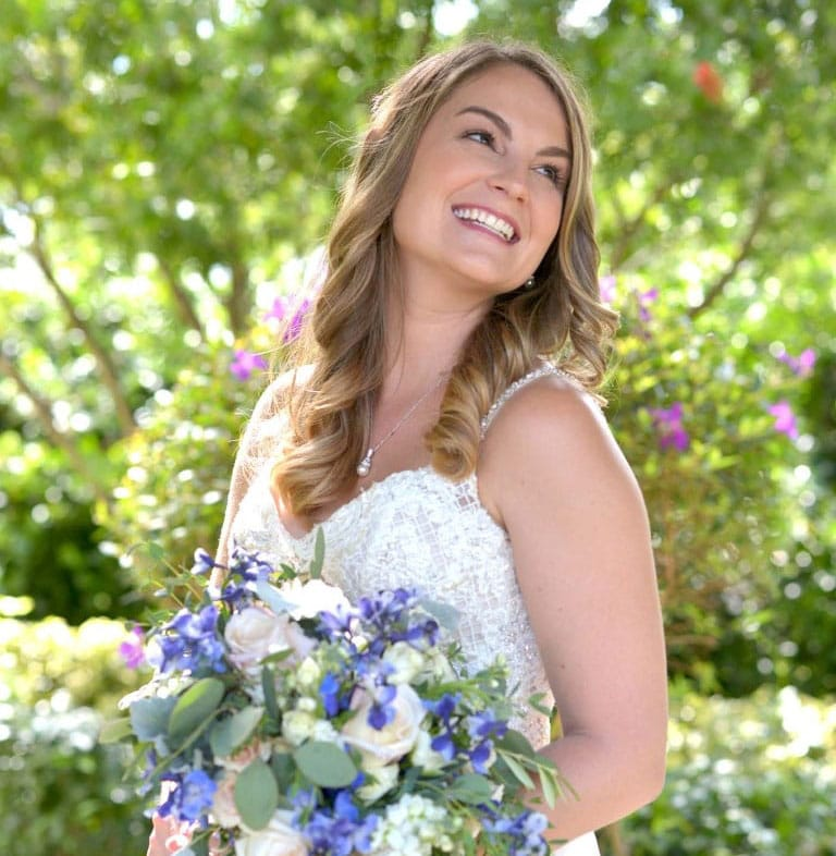 bride holding purple and white bouquet while smiling and looking over her shoulder