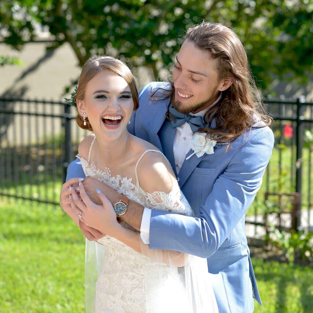 groom in blue tux hugging bride in lace dress