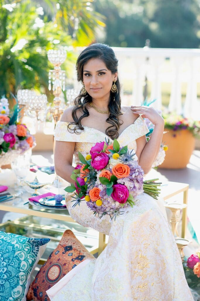 bride sitting on a glass table holding her flower bouquet