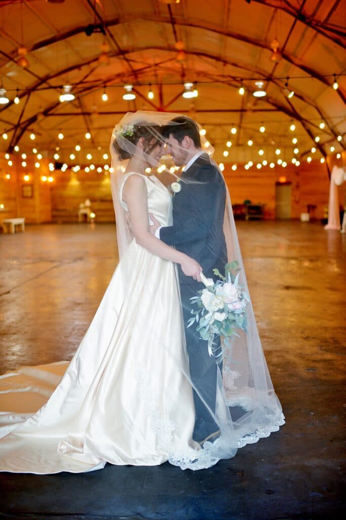 bride and groom holding each other while the brides veil wraps around them