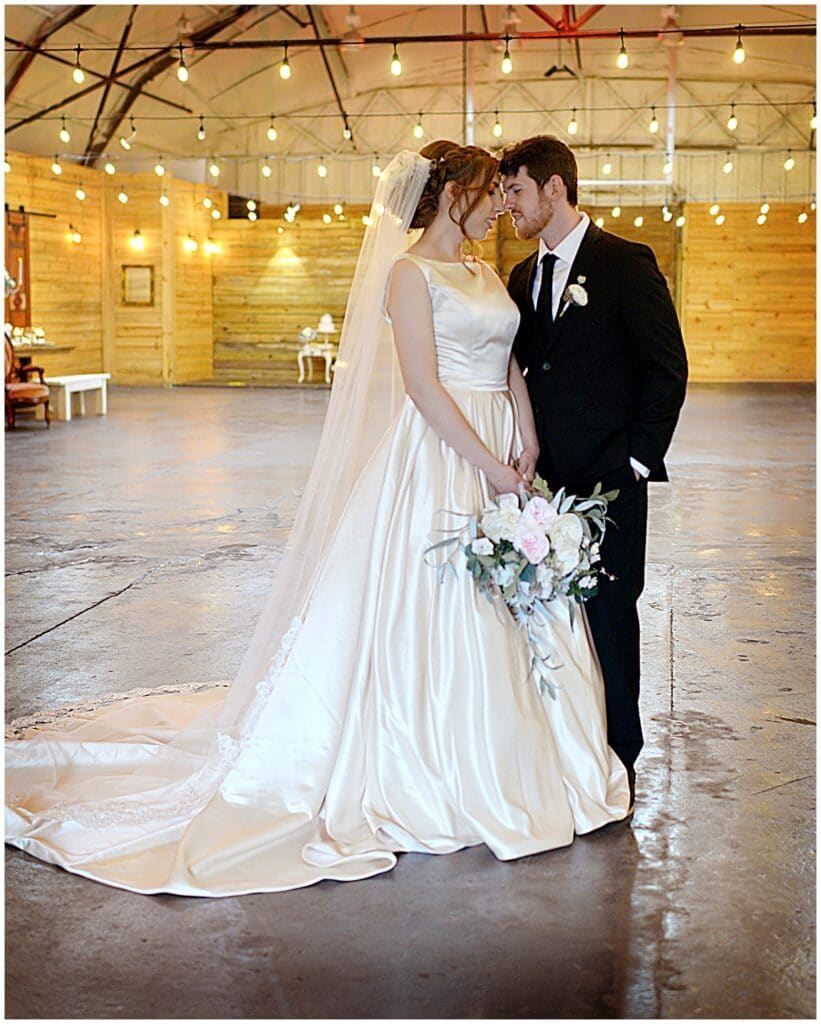 bride and groom standing inside in a large room that will be set up for their wedding reception