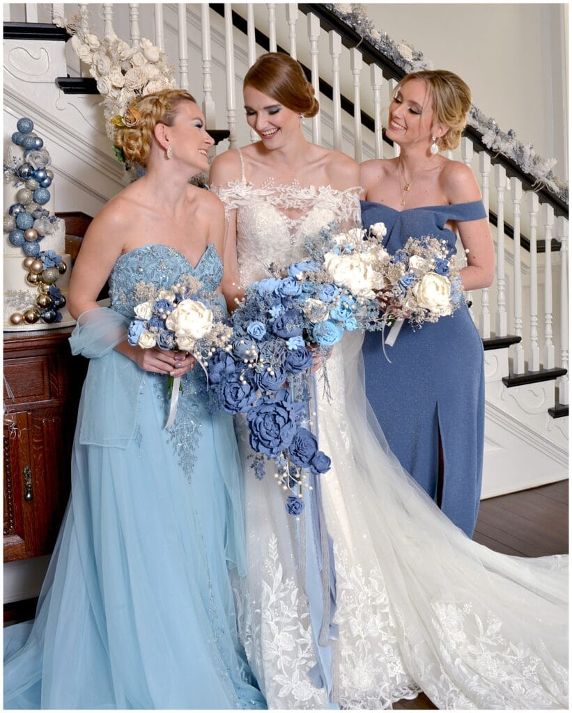 bride smiling with her bridesmaids while everyone holds their flower bouquets