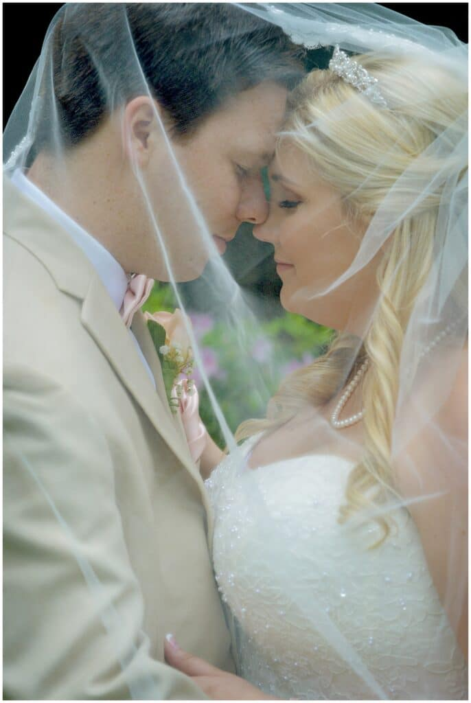 bride and groom embracing each other with the wife's veil wrapped around them