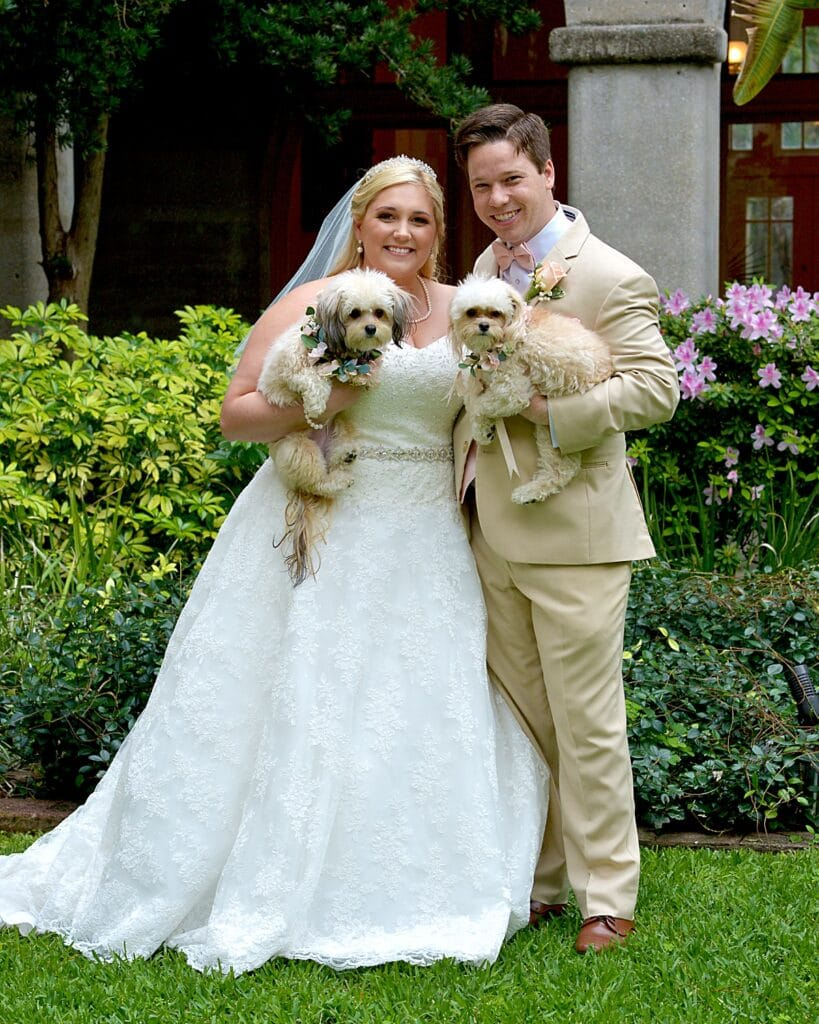 bride and groom smiling while holding their two little dogs
