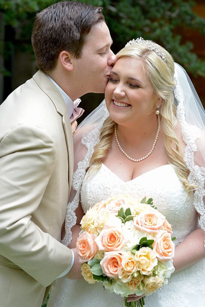 groom kissing his bride on her cheek while she smiles