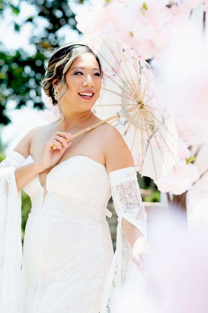bride holding a pink flower umbrella over her shoulder to protect her from the sun