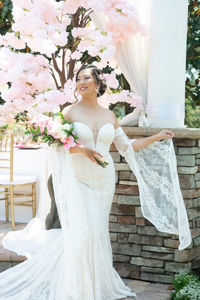 bride standing outside holding her flower bouquet featuring pink flowers which matches the flowers on the large tree behind her