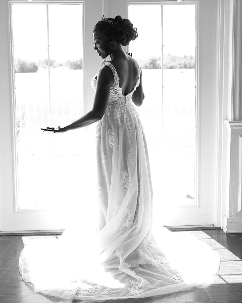 bride standing in her wedding dress in front of two large glass doors looking down at her engagement ring
