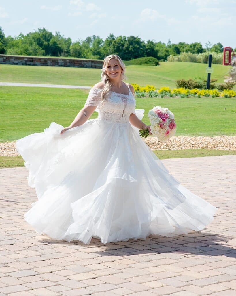 bride standing in her wedding dress outside with the golf course behind her