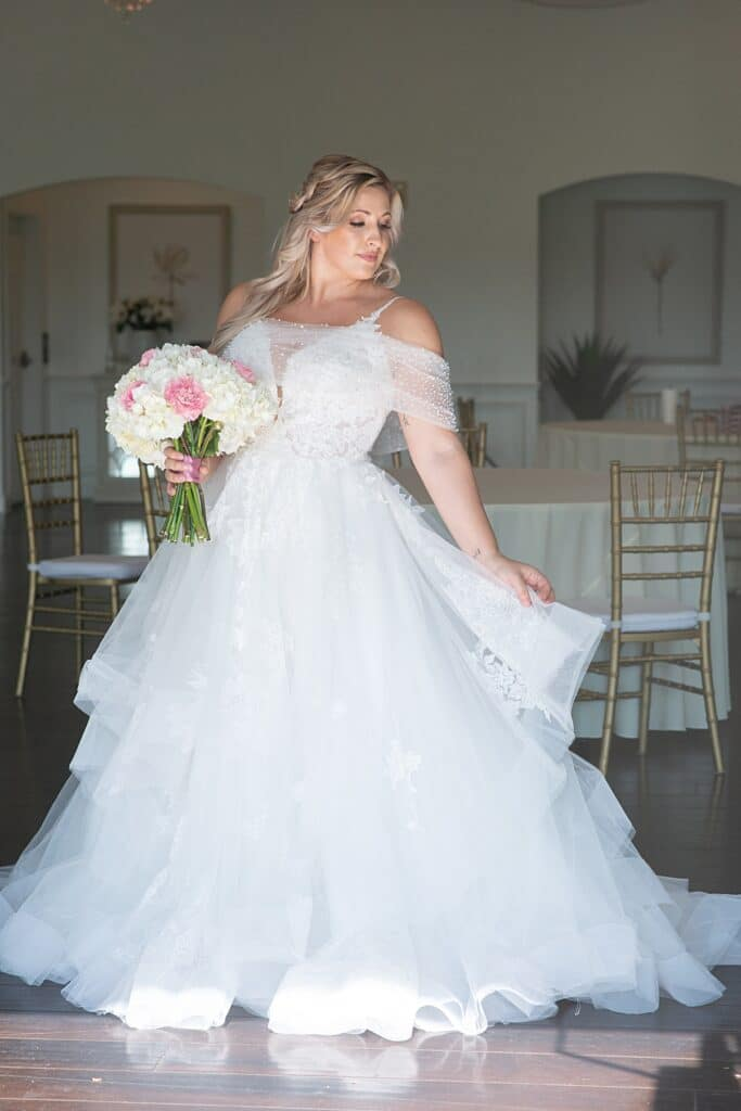 bride in her wedding dress holding her white and pink flower bouquet