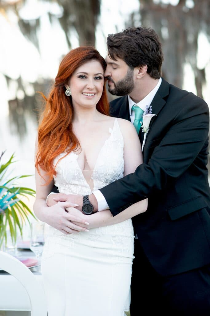 groom holding his bride while she smiles
