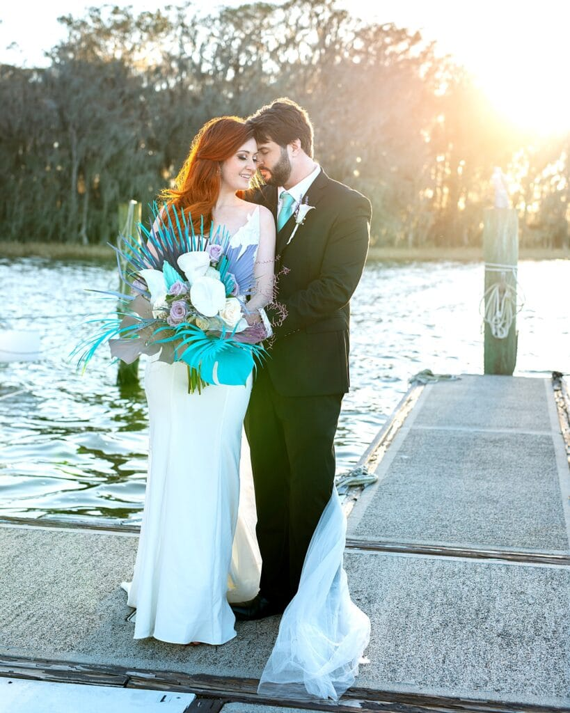 bride and groom standing on a dock sticking out into a river