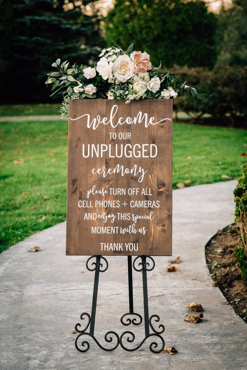 A Chair Affair - Unplugged Ceremony wood sign with flowers outside