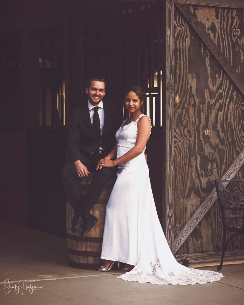 Seas Your Day Events - groom sitting on barrel with bride standing next to barn door