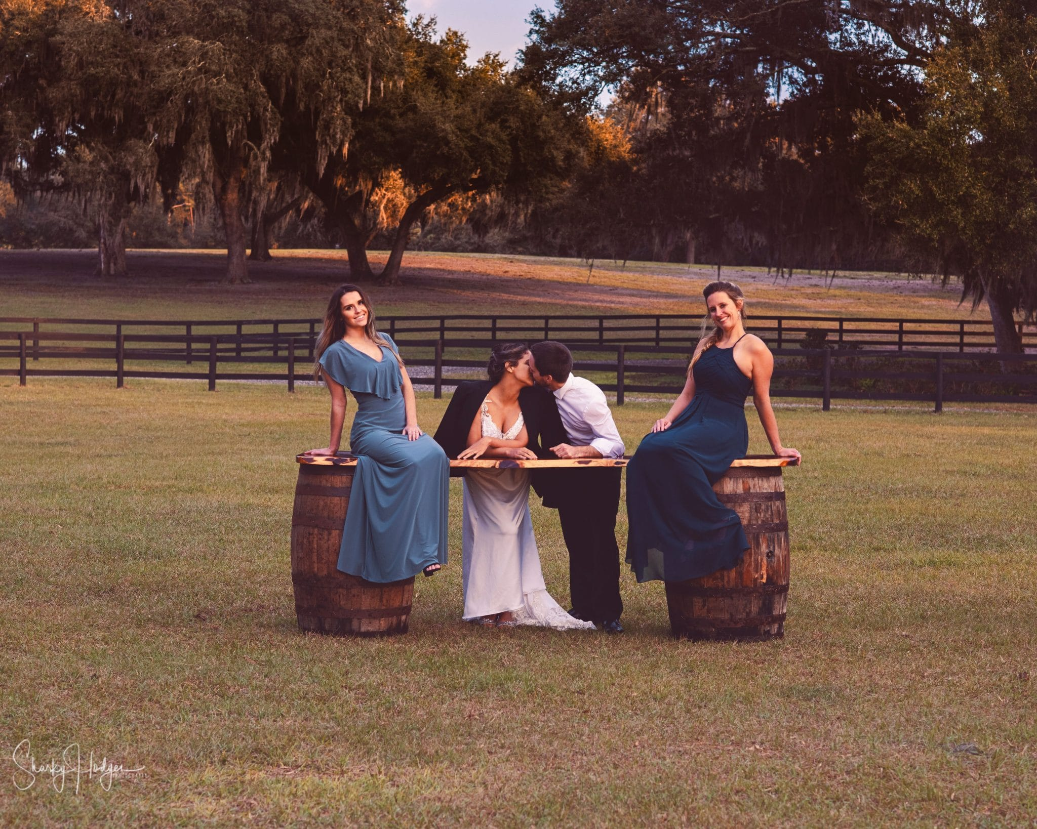 Seas Your Day Events - bride and groom standing in field kissing with bridesmaids sitting on barrels