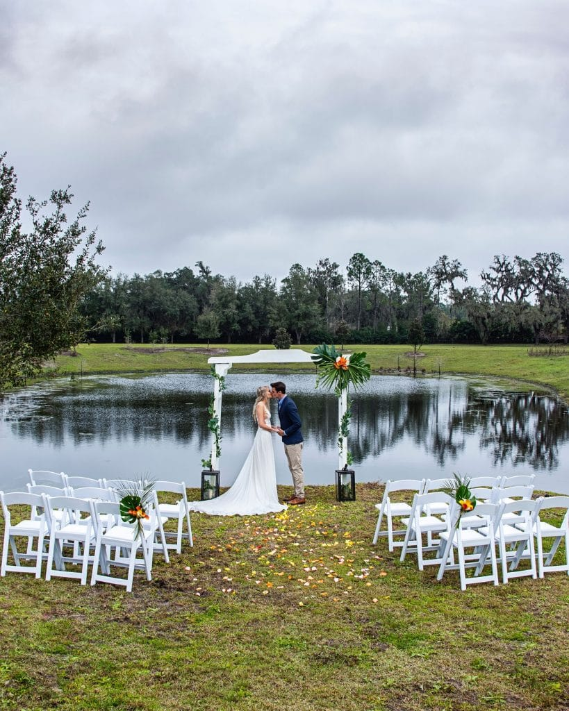 Seas Your Day Events - bride & groom kissing under arbor in front of a lake ceremony