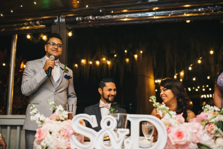 White Rose Entertainment-Rudy & Marta Photography-groomsman giving speech standing in front of bride & groom table at reception