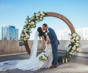 Sparkleigh-Productions-Bride and Groom kissing in front of wooden floral ring at top of building.
