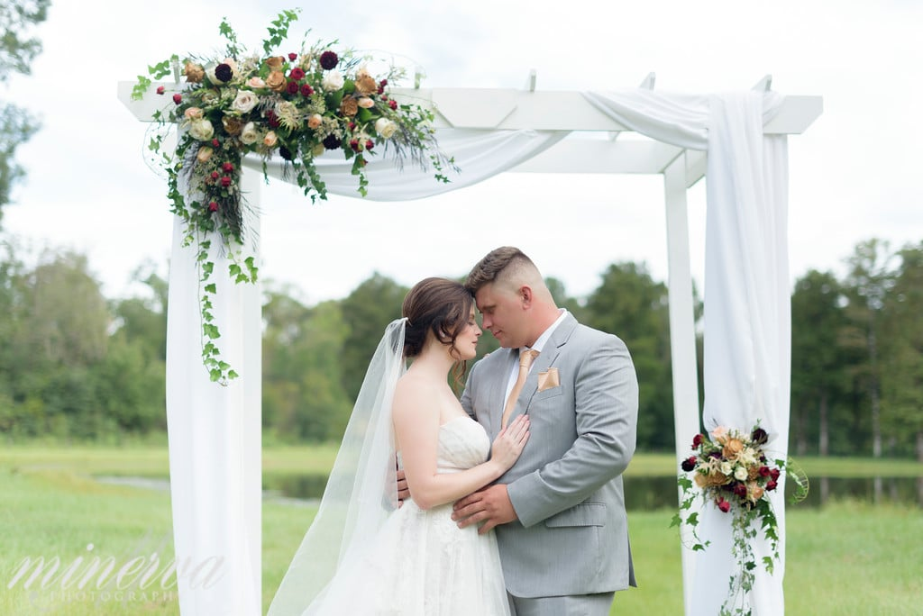 bride and groom under white arch with flowers